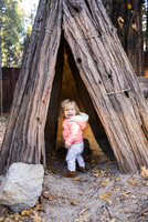 Caucasian baby girl playing in teepee