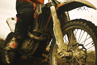 Close up of man riding muddy dirt bike