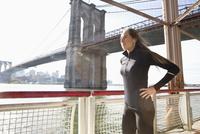 Caucasian runner standing on waterfront, New York, New York, United States