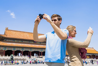 Caucasian couple photographing historical building, Beijing, Beijing Municipality, China
