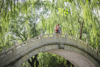 Caucasian couple photographing on bridge