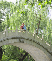 Caucasian couple hugging on bridge