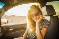 Hispanic woman smiling in car