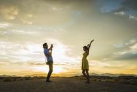 Hispanic man photographing girlfriend on remote road