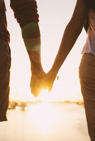 Hispanic couple holding hands at sunset