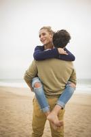 Hispanic man carrying girlfriend on beach