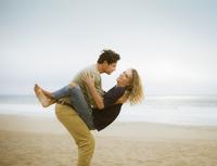 Hispanic man holding girlfriend on beach