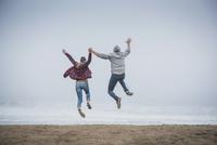 Hispanic couple jumping on beach