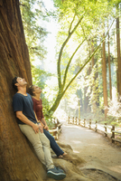 Hispanic couple leaning on tree in forest