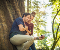 Hispanic couple taking selfie in forest