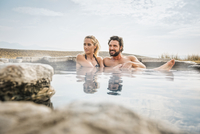 Hispanic couple sitting in pool