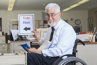 Caucasian businessman holding voting sign in office