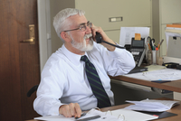 Caucasian businessman talking on phone in office