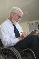 Caucasian businessman writing on notepad in office
