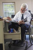 Caucasian businessman reading binder at desk