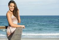 Hispanic woman standing on beach pier
