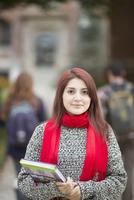 Hispanic college student holding books on campus