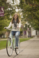 Caucasian college student riding bicycle on campus