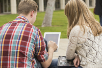 Caucasian couple using digital tablet outdoors