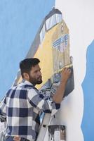 Hispanic artist painting mural wall
