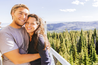 Caucasian couple hugging over forest treetops
