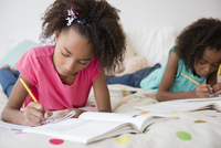 Mixed race sisters doing homework on bed