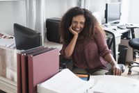 Black businesswoman smiling at office desk