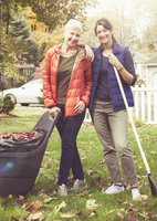 Mother and daughter raking leaves in backyard