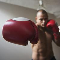 Hispanic boxer punching with boxing gloves
