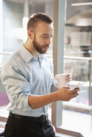 Caucasian businessman using cell phone in office