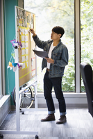 Asian businessman using board in office