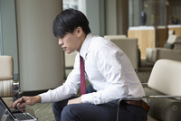 Asian businessman using laptop in office lounge