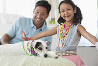 Caucasian father and daughter playing dress-up with dog
