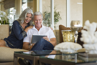 Older Caucasian couple using digital tablet on sofa