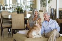 Older Caucasian couple petting dog
