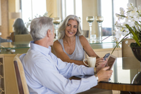 Older Caucasian couple talking at table