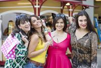 Smiling Hispanic women holding shopping bags