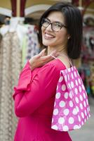 Hispanic woman carrying shopping bag outdoors