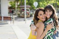 Hispanic women hugging outdoors