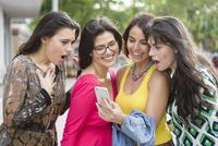 Hispanic women using cell phone outdoors