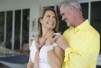 Older Caucasian couple hugging outdoors