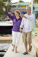 Older Caucasian couple waving from pier