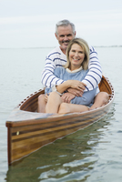 Older Caucasian couple hugging in canoe