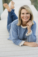 Older Caucasian woman laying on pier