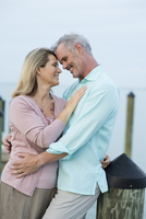 Older Caucasian woman hugging on pier