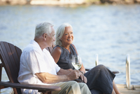 Older Caucasian couple sitting on pier