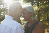 Older Caucasian couple hugging outdoors