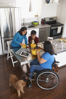 Indian mother in wheelchair baking in kitchen with children