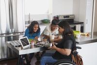 Indian mother in wheelchair baking in kitchen with children