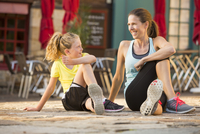Caucasian mother and daughter stretching outdoors